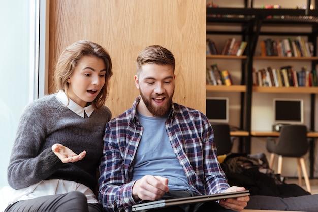 Dwóch młodych studentów korzystających z komputera typu tablet