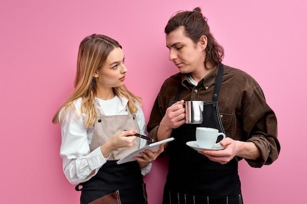 Dwóch młodych studentów pracuje jako kelnerzy, stojąc i rozmawiając podczas pracy