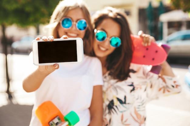 Dwóch młodych stylowy uśmiechający się hipis brunetka w słoneczny letni dzień w hipster ubrania ze stawianiem deskorolka grosza
