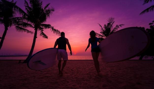 Dwóch młodych surferów udających się do morza z desek surfingowych