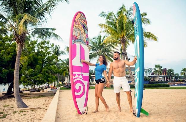 Dwóch młodych surferów z deskami na plaży
