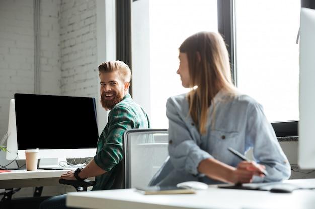 Dwóch młodych szczęśliwych kolegów pracuje w biurze