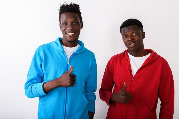 Dwóch młodych szczęśliwych przyjaciół uśmiecha się, podczas gdy dają kciuki do góry