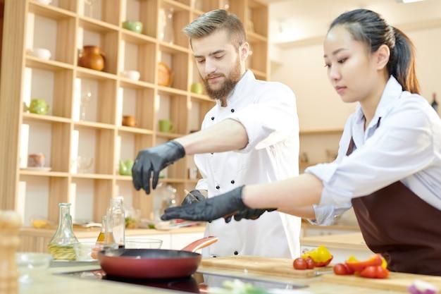 Dwóch młodych szefów kuchni pracujących w kuchni