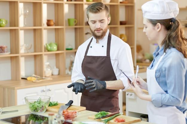 Dwóch młodych szefów kuchni w kuchni restauracji