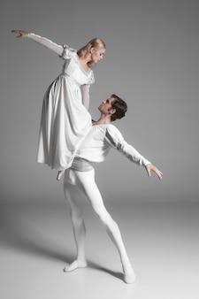 Dwóch młodych tancerzy baletowych ćwiczących. atrakcyjni wykonawcy tańca w bieli
