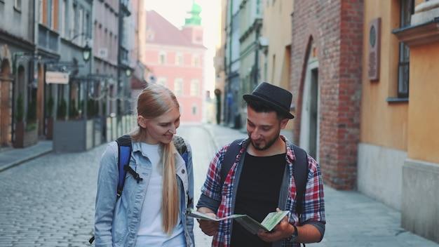 Dwóch młodych turystów sprawdzających mapę podczas spaceru główną ulicą turystyczną. wcześnie rano wybierają się na zwiedzanie.