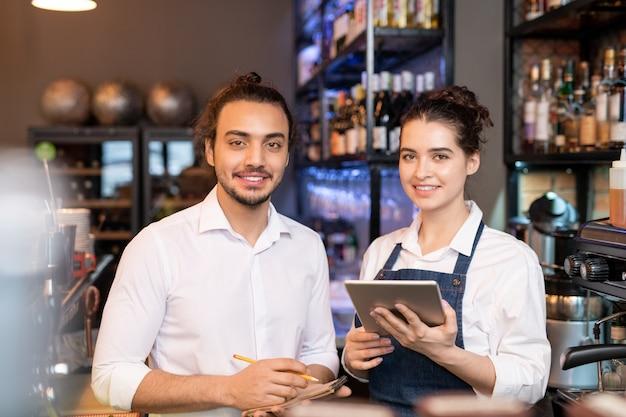 Dwóch młodych uśmiechniętych przedstawicieli personelu usług stojących przed kamerą na tle półek z butelkami wina
