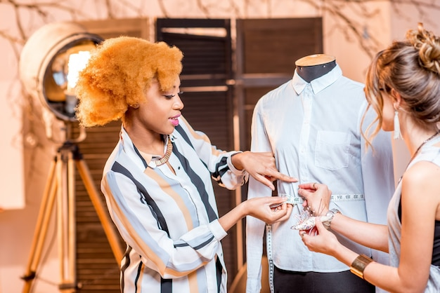 Dwóch młodych wieloetnicznych projektantów mody pracujących z manekinem w studio