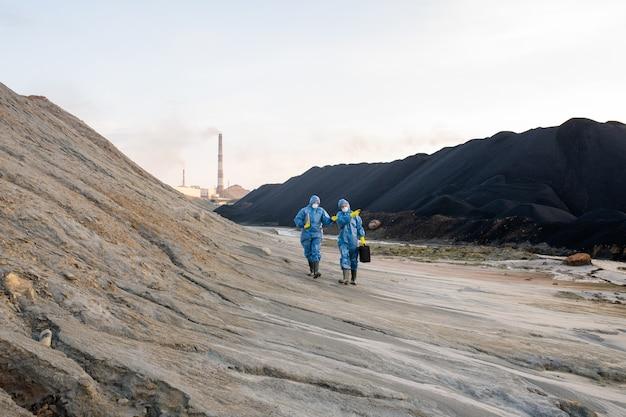 Dwóch młodych współczesnych ekologów w ochronnych strojach roboczych porusza się po wzgórzu, badając niebezpieczne terytorium i omawiając jego obrzeża