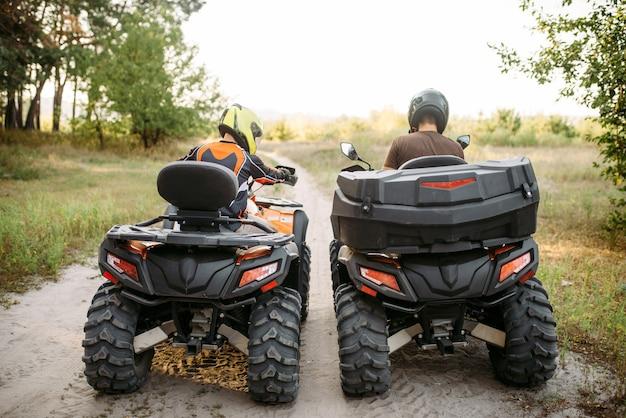Dwóch motocyklistów atv w kaskach, widok z tyłu. freeride na quadach, sporty ekstremalne i podróże, letnia przygoda na quadach
