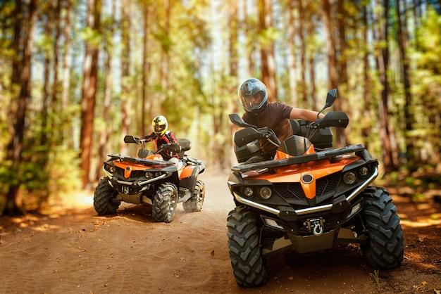 Dwóch motocyklistów atv w kaskach, wyścig prędkości w lesie, widok z przodu. jazda na quadzie, sporty ekstremalne i podróże, przygoda na quadach w terenie