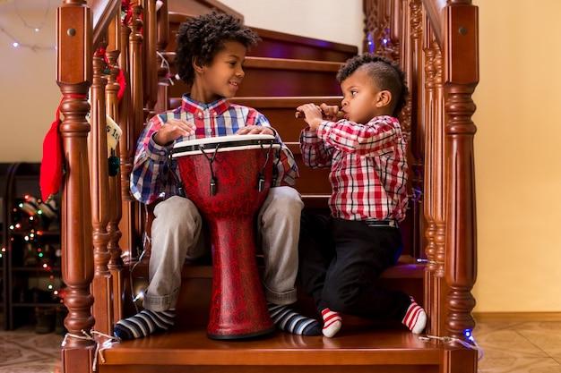 Dwóch mulatów grających muzykę dzieciaki grają muzykę na boże narodzenie, zachowując rytm brata prawie jak umiejętn...