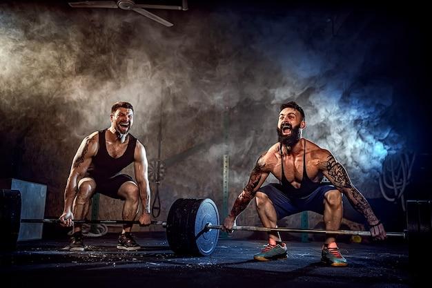 Dwóch muskularnych, brodatych sportowców wytatuowanych trenujących, podnoszących ciężki pasek z dymem na siłowni