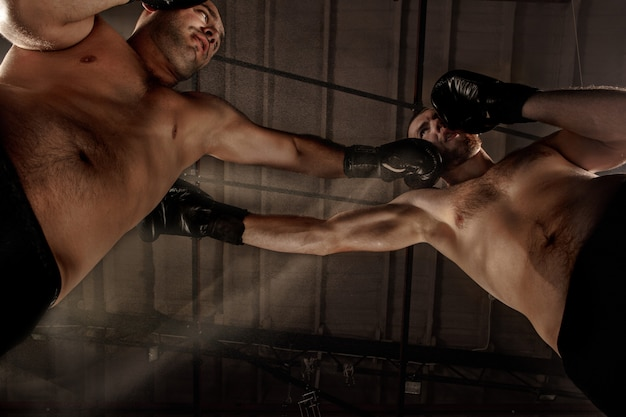 Dwóch muskularnych mężczyzn walczących, kulturystów bijących się nawzajem, trenujących sztuki walki, boks, jiu jitsu