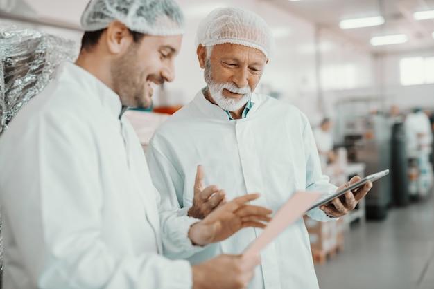 Dwóch nadzorców omawia jakość żywności w zakładzie spożywczym. młodszy jeden trzyma folder z danymi, a starszy trzyma tablet.
