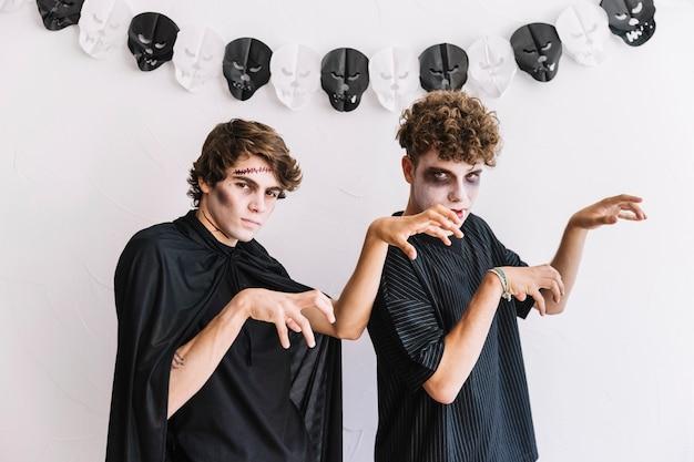 Dwóch nastolatków w halloween ponuro zachowuje się jak zombie