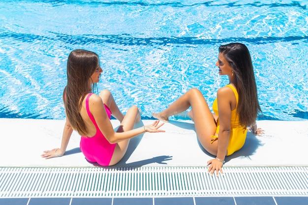 Dwóch nastolatków w strojach kąpielowych w basenie