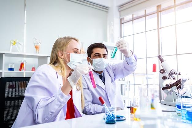 Dwóch naukowców pracuje, patrząc na probówkę z próbką w laboratorium chemicznym naukowiec lub młoda naukowiec płci męskiej i żeńskiej, przeprowadzają badania w tle analizy laboratoryjnej