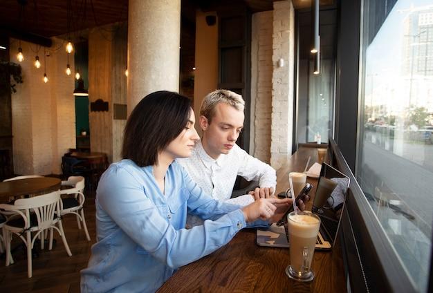Dwóch niezależnych pracowników w kawiarni. brunetka kobieta pokazuje coś w swoim smartfonie i wskazuje na ekranie, człowiek słucha. koncepcja podejmowania decyzji. kubek latte i szary laptop na stole.