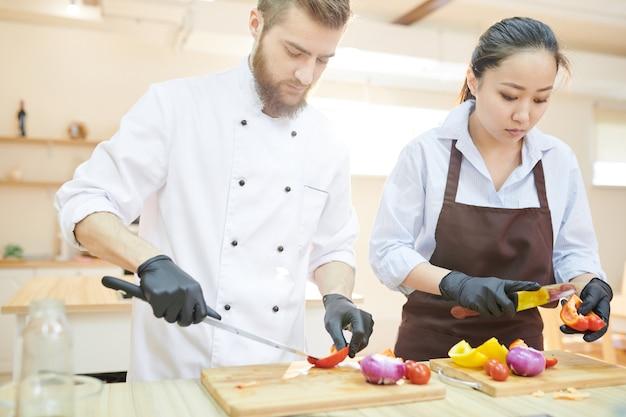 Dwóch nowoczesnych szefów kuchni pracujących w kuchni