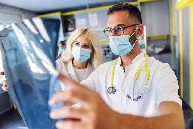 Dwóch oddanych ciężko pracujących inteligentnych kolegów trzymających prześwietlenie płuc pacjenta i oglądające je.
