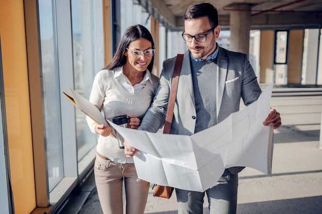 Dwóch oddanych pracowitych, pozytywnych architektów spacerujących po budynku w trakcie budowy i przeglądających plany. budowa nowego centrum biznesowego.