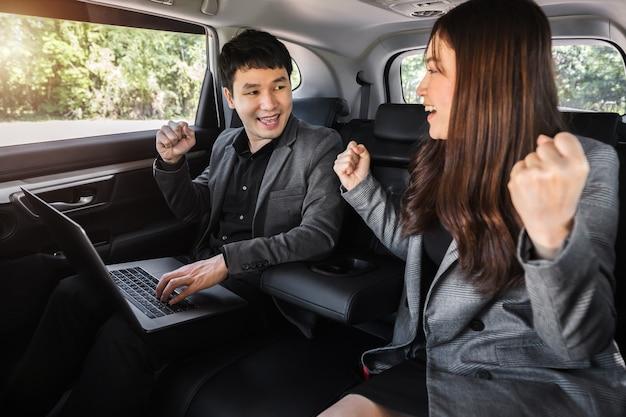 Dwóch odnoszących sukcesy biznesmenów i kobiet pracujących z laptopem, siedząc na tylnym siedzeniu samochodu