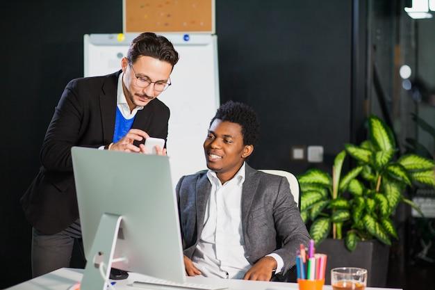 Dwóch odnoszących sukcesy biznesmenów w biurze pracuje razem oglądać monitor komputera i inteligentny telefon komórkowy