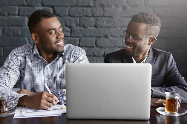 Dwóch odnoszących sukcesy i doświadczonych afroamerykańskich menedżerów uśmiechających się radośnie