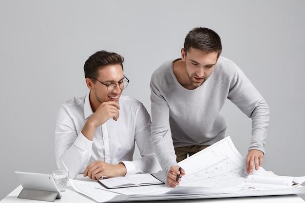 Dwóch odnoszących sukcesy zawodowych konstruktorów płci męskiej studiujących plany w przestronnym, oświetlonym biurze
