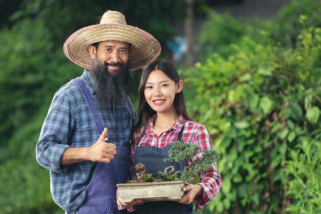 Dwóch ogrodników uśmiecha się trzymając garnek roślin