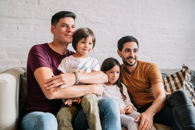 Dwóch ojców i ich dzieci bawią się razem, oglądając filmy na domowej kanapie. koncepcja rodziny.