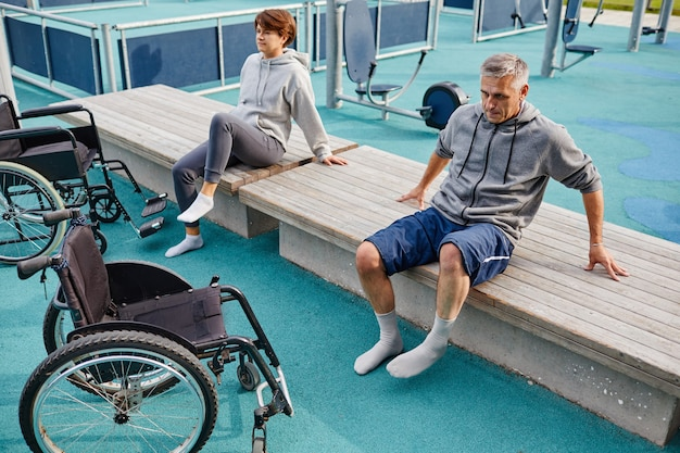 Dwóch pacjentów siedzących na ławce na świeżym powietrzu odpoczywających po ćwiczeniach sportowych regenerują się z ...