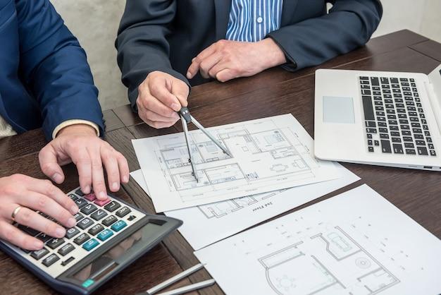 Dwóch partnerów architektów pracujących w houme rysuje konstrukcję z laptopem i narzędziami w biurze. projekt architekta