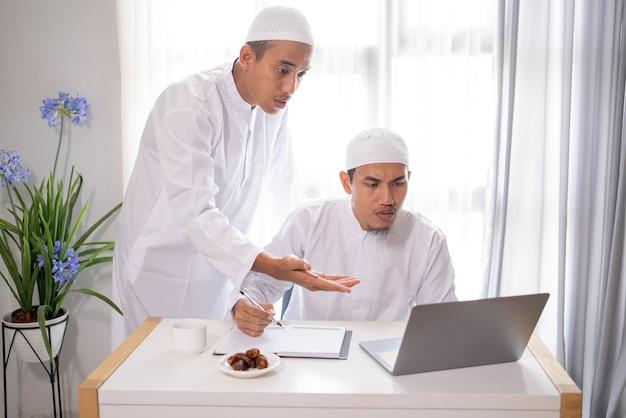 Dwóch partnerów biznesowych muzułmańskich dyskusji i spotkania przy użyciu laptopa razem