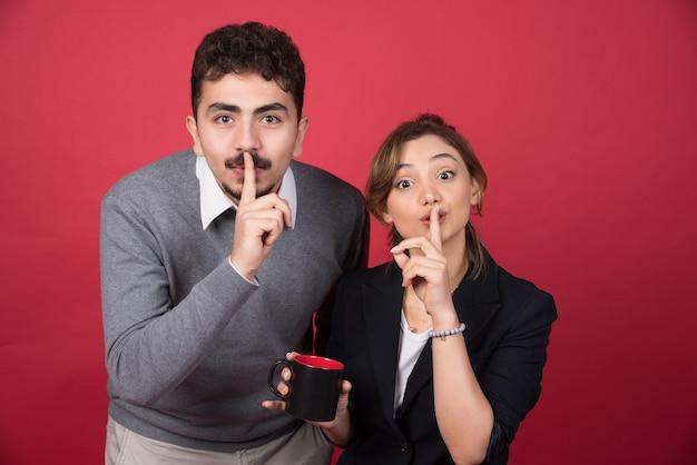 Dwóch partnerów biznesowych podając znak ciszy na czerwonej ścianie