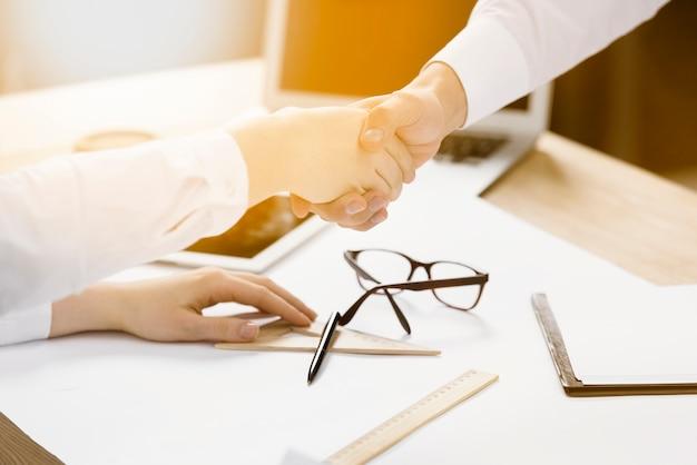 Dwóch partnerów biznesowych potrząsając sobie nawzajem ręce nad biurkiem
