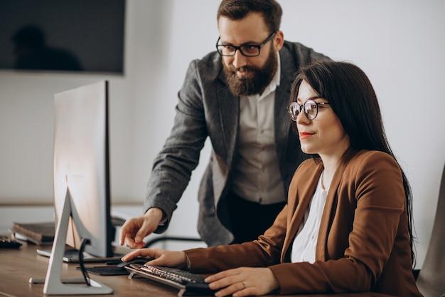 Dwóch partnerów biznesowych pracujących razem w biurze na komputerze