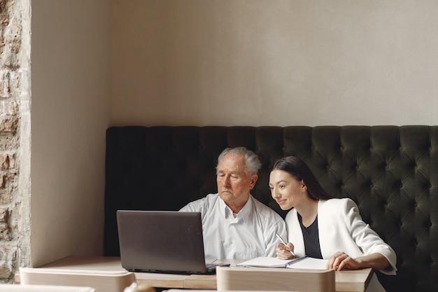 Dwóch partnerów biznesowych pracujących z laptopem w kawiarni