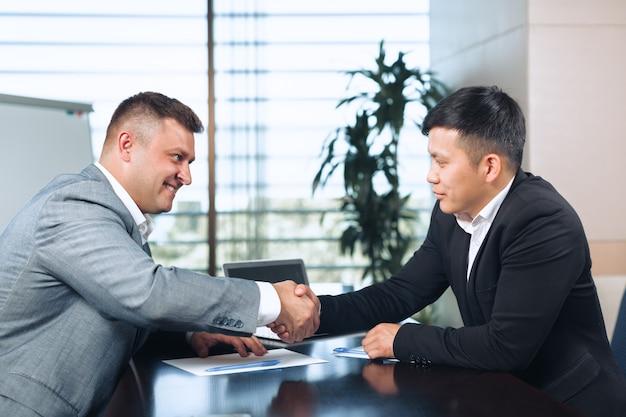 Dwóch partnerów biznesowych siedzi przy stole i pracuje razem.
