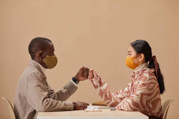 Dwóch partnerów biznesowych w ochronnych maskach siedzi przy stole, witając się przed spotkaniem