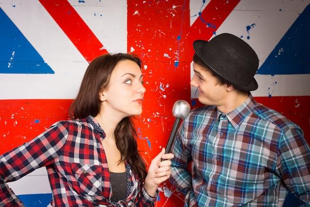 Dwóch performerów wykonujących brytyjską komedię, stojących przed namalowanym na ścianie union jackiem za pomocą mikrofonu w patriotycznych ubraniach i meloniku