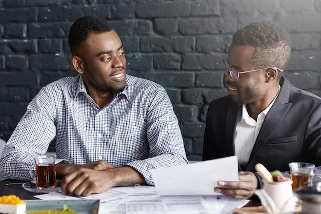 Dwóch pewnych siebie i odnoszących sukcesy ciemnoskórych partnerów biznesowych prowadzi miłą rozmowę