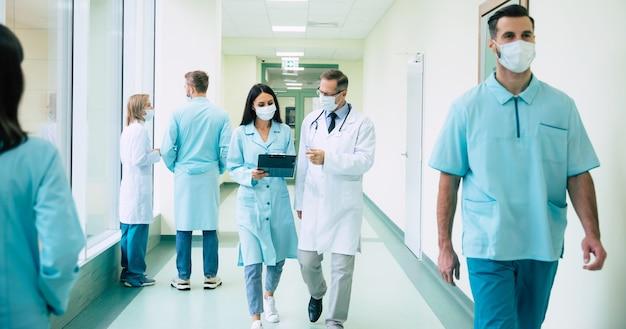 Dwóch pewnych siebie lekarzy w ochronnych maskach medycznych omawia niektóre metody leczenia podczas spaceru po szpitalnym korytarzu z innymi kolegami w pobliżu