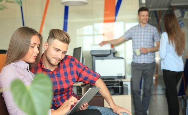 Dwóch pewnych siebie młodych ludzi patrzących na touchpad, podczas gdy ich koledzy pracują w tle
