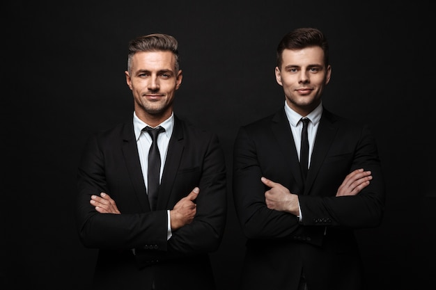 Dwóch pewnych siebie, przystojnych biznesmenów w garniturze, stojący na białym tle nad czarną ścianą, z założonymi rękoma