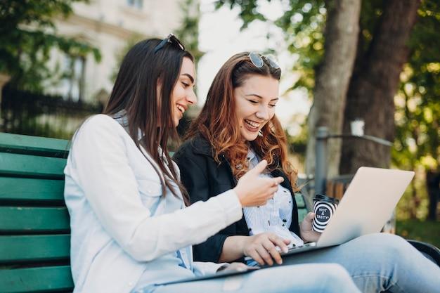 Dwóch pięknych młodych przyjaciół śmiejąc się, patrząc na ekran laptopa siedząc na ławce w parku, pijąc kawę.