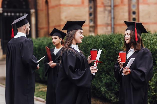 Dwóch pięknych studentów mówiących o egzaminach. ukończone wykształcenie.