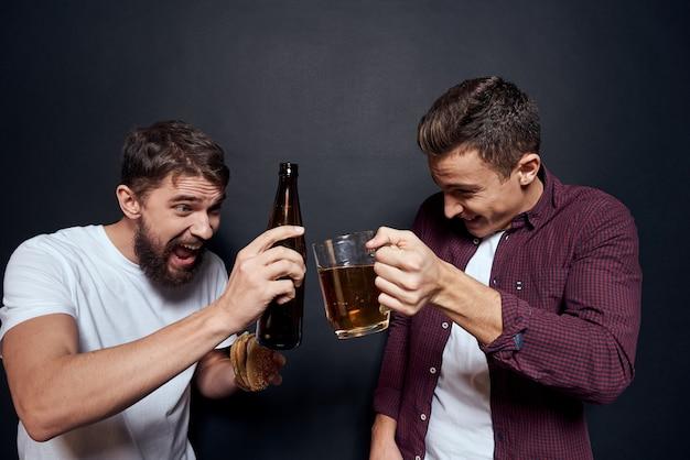 Dwóch pijanych przyjaciół pije piwo na imprezie